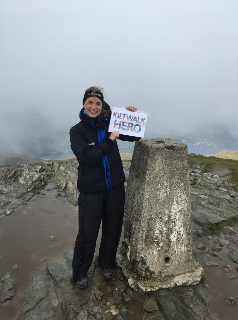"""Debbie is smiling, standing on the top of Ben Lomond. She is holding up a sign which reads """"Kiltwalk Hero"""". It is a cloudy day, and her hair is blowing in the wind."""